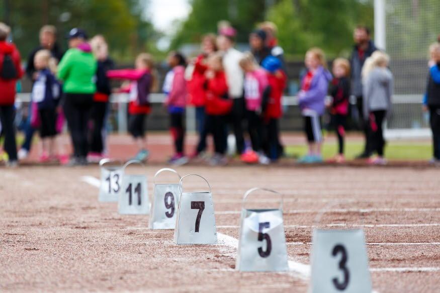 En friidrottsarena med barn i bakgrunden, startblock för sprintlopp