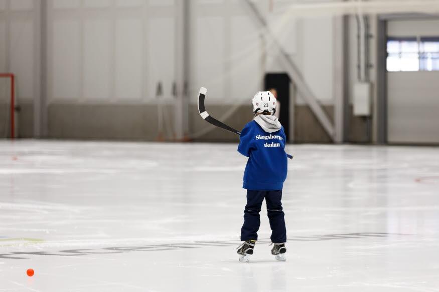 Ett barn på skridskor med klubba och hjälm har ryggen vänd mot kameran på isen.