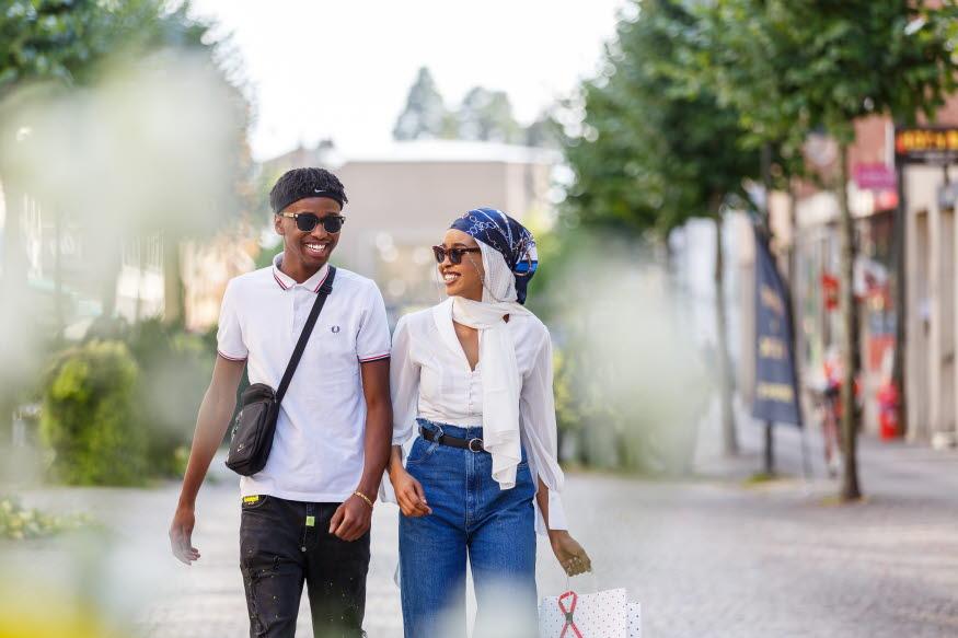 Två ungdomar skrattar på stan. De ler.