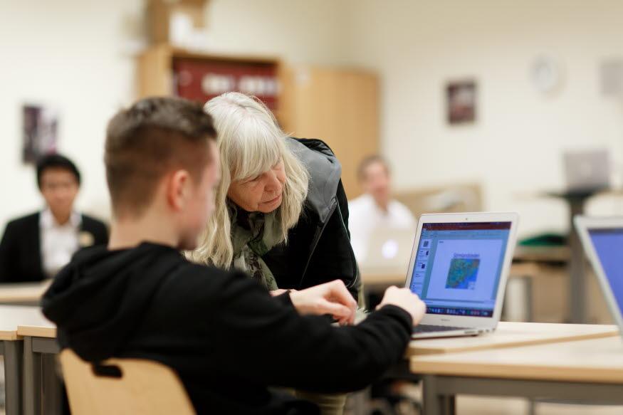 Lärare hjälper elev vid en dator