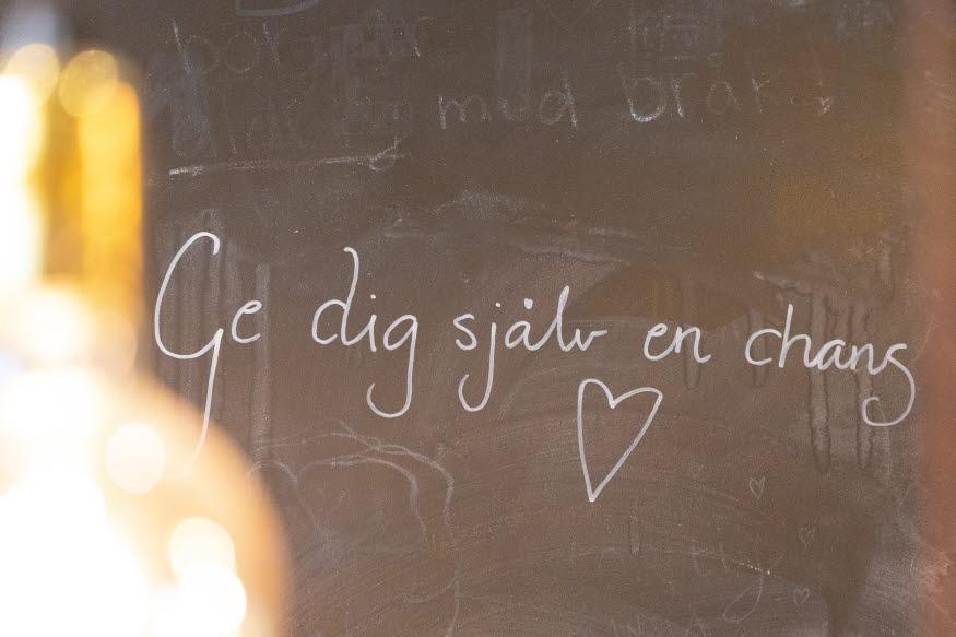Text på svart vägg med krita: Ge dig själv en chans. Ett hjärta är ritat.