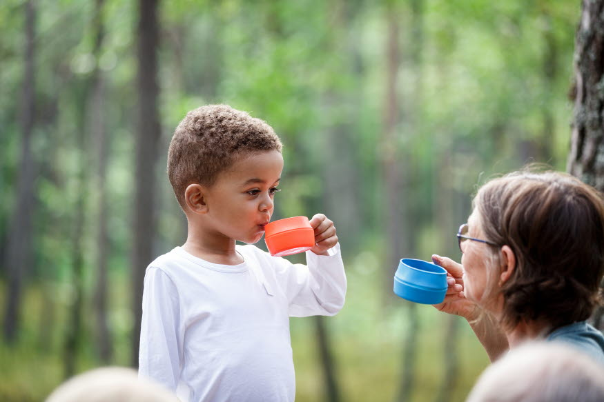 Ett barn och en äldre kvinna tar en fikapaus ute i naturen och dricker från varsin kåsa.