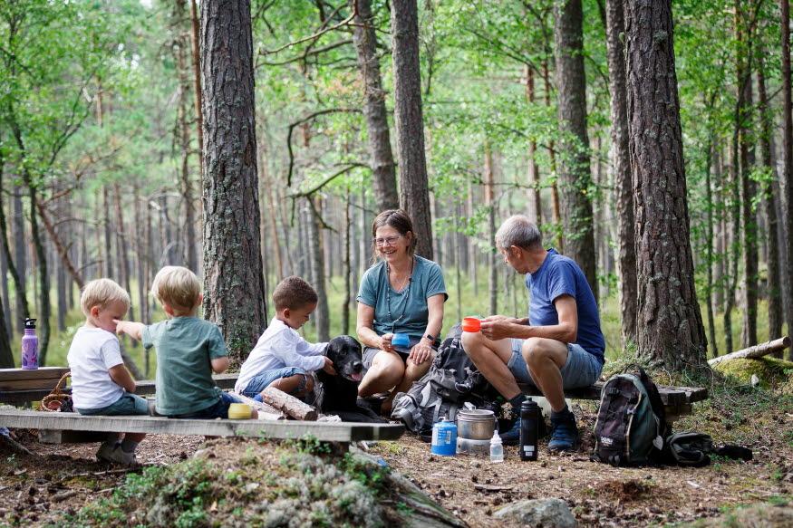 Flera personer, gamla som vuxna, och en hund sitter i en skog och fikar.